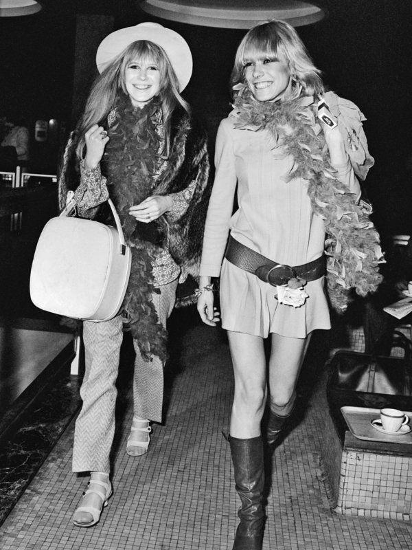 """世界中を虜にしたグルーピー流インパクトコーデ  1960年代後半、""""ストーンズの女""""としてマリアンヌと#BFF関係だったアニタ・パレンバーグ(右)と。(アニタはブライアン・ジョーンズ→キース・リチャーズと交際)。ローリング・ストーンズを一気におしゃれバンドに変えたといわれるふたりのファッションセンスは抜群。マリアンヌは、柄on柄コーデにファージャケットを羽織り、フェザー飾りというタッキースタイル。アニタは太ベルトをアクセントにした超ミニワンピに、同じくフェザー飾りをオン。ロックスターの彼女的インパクトスタイルは、当時、世界中の女性の憧れの的。"""