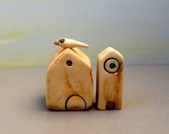 Dit is een keramiek en aardewerk handgemaakte beeld. Deze keramische sculptuur bevat 8 witte klei miniatuur huizen als een prachtige miniatuur-buurt. Het bevat ook 3 bruine en witte klei bomen, en een kleine keramische vogel. Alle zijn aangesloten op een steen grijs natuurlijke strand.  Dit wordt gemaakt in een rustieke en strand stijl en is een van een soort sculptuur.  De huizen zijn soort oude en rustieke kijken, ze hebben een heleboel scheurtjes die ik gemarkeerd met donkere…