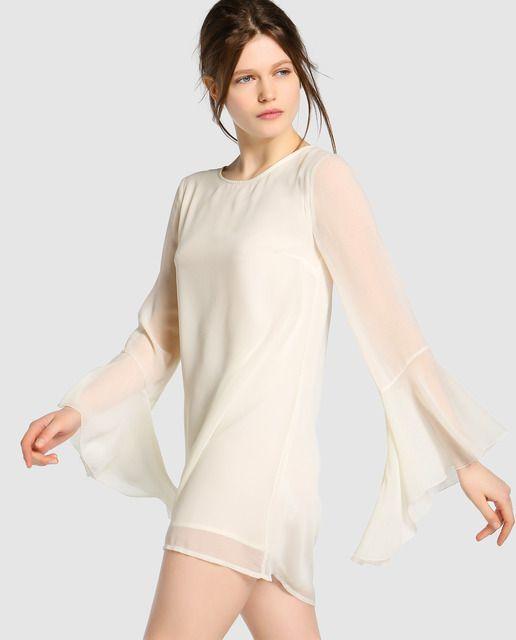 Vestido corto de gasa en color crema. Tiene manga larga campana, escote redondo y abertura con botón en la espalda.