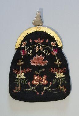 Kjolsäck till dräkt för kvinna från Älvros socken, Härjedalen. Framstycke av svart ylletyg, vävt i tuskaft. Broderad med ullgarn i vitt, två rosa toner, grönt samt något blårött. Fritt broderi med två centralt placerade större blommor och blomsterslingor runtom, sytt med stjälksöm, schattérsöm och plattsöm. Årtalet 1836 sytt med vitt garn och stjälksöm. Bygel med snäpplås, framdel av mässing och bakdel av stål. Framdelen med graverad dekor. Upptill gångjärnsmekanism med krok...