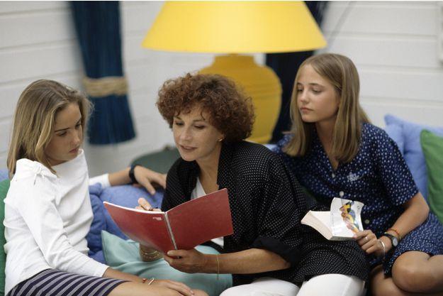 En 1993, chez elle, Marlène lit entourée de ses filles Eva et Joy.