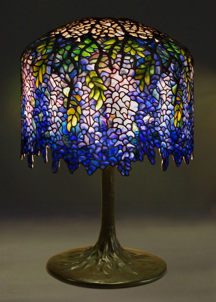 Tiffany Wisteria art nouveau style table lamp, c. 1902. Leaded glass and bronze. Wisteria Lamp, 1901-1902, designed by Clara Driscoll. Illuminated from within by the newly invented light bulb. This lamp is shaped so that the stained glass resembles the drooping purple flowers of the wisteria plant. The striking naturalism is reinforced by the lamp's bronze stand, which is shaped like a thick vine or tree trunk with spreading roots at the base.