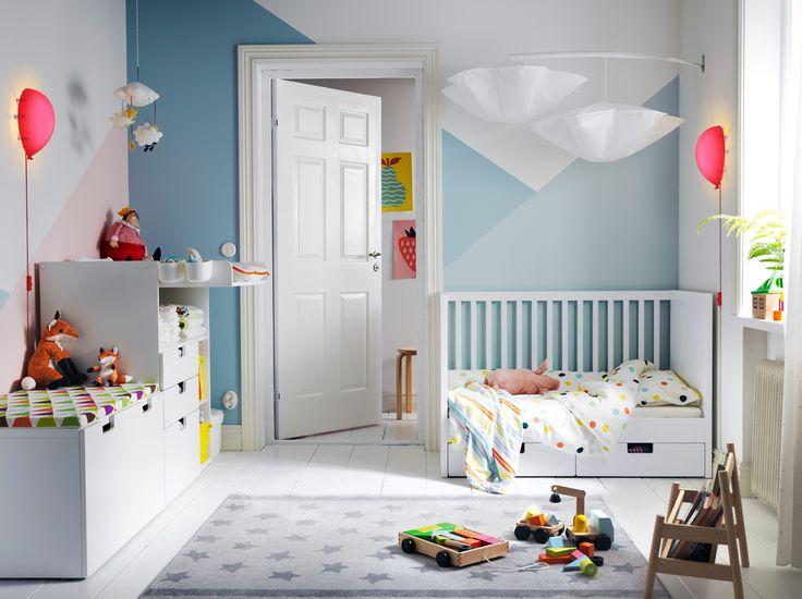 Detská izba s bielou detskou postieľkou s dvoma zásuvkami, prebaľovacím pultom a úložnou lavicou s veľkou zásuvkou na kolieskach.