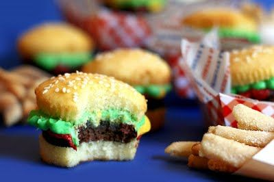 Simple buger cupcake: cut a plain sponge cupcake in half, cut a 'burger' disc from a chocolate cupcake or chocolate brownie and stick onto the lower 'bun' with 'ketchup' (jam), top with (green buttercream) lettuce and the top half of the cake, sprinkle with seasame seeds or demerara.