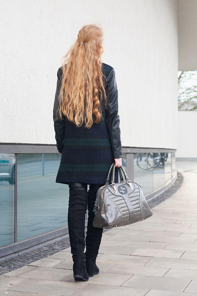 Deutsche Modebloggerin Fee Schoenwald trägt hier ein Winter Outfit, bestehend aus einem dunkelgrünen Tartan Mantel, einer Lederhose und Wildleder Overknees in schwarz. Dazu trägt sie eine Gucci Lack Handtasche. Entstanden in Oldenburg.