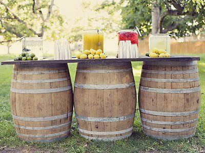 A vintage inspired outside wedding idea! Three wooden barrels placed next to each other and a thin piece of wood to placed across them, makes the perfect outdoor bar, food station, or place-card table! Dress this up with burlap and lace and watch your vintage wedding come to life!