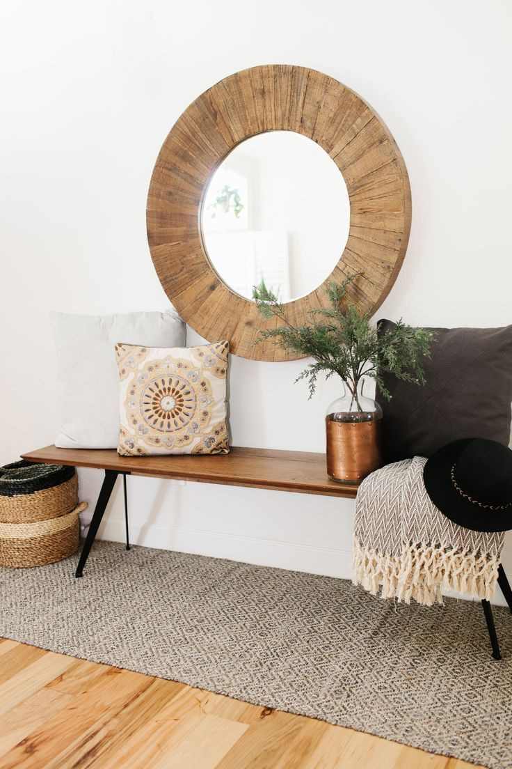 oversize round wood mirror with a midcentury modern style bench and cozy pillows and throws to add warmth