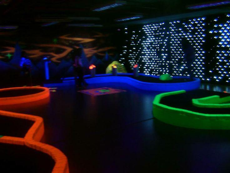 De Tee & Putt minigolf baan in Dubai. De ruimte is helemaal donker en wordt verlicht door blacklight lampen.