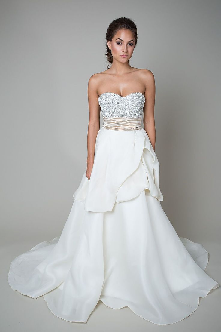 This two-piece/bridal separate wedding dress features a hand-beaded bodice  of pearls and rhinestones, a sweetheart neckline, a natural waist defined  with a champagne ruched belt, and a silk gazar peplum skirt with a chapel  train.      * Photographed In:Off White / Pearl / Champagne     * Color Options:Off-White / Ivory     * Fabric:Silk / Gazar / Beading     * Silhouette:Ball Gown     * Neckline:Strapless Sweetheart     * Waistline:Natural     * Details:Two-piece / Bridal Separate…
