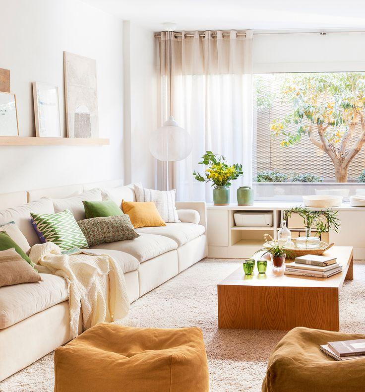 Estar con sofá en color crudo y balda con cuadros encima