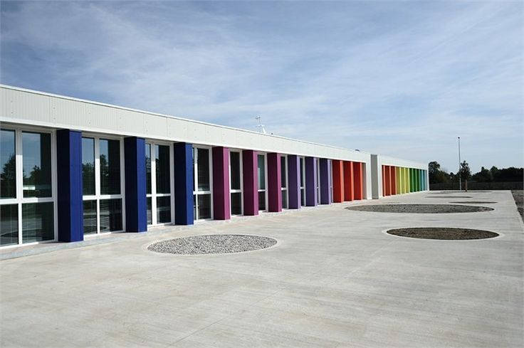 """Montessori school building MADE IN 50 DAYS for the earthquake emergency in Emilia Romagna. From the square, the building has a concrete wall that acts as a fence. A wall strong, imposing, rough, he wants to convey an idea of strength and protection for parents who bring their children to school. Inside the fence instead is a """"world"""" colored. A series of color-pillars marks the main facade. Just Beautiful."""