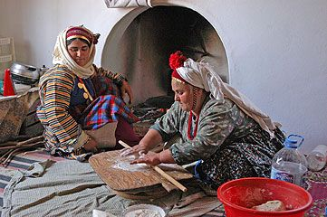 "Turkish Women preparing the traditional ""yufka"" (a thin dough).."