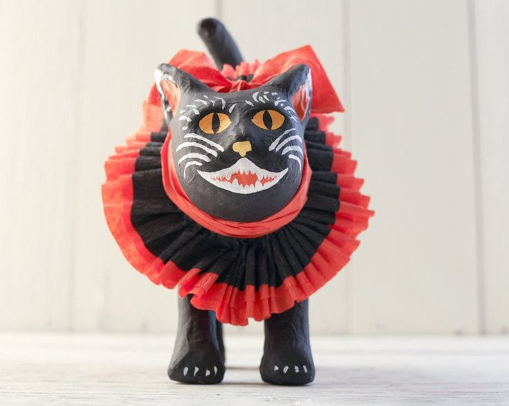 Make a painted paper mache Halloween cat to guard your candy stash!  This 1920s style kitty has a folky face, and a charming ruffle of crepe paper around his neck in classic orange and black.  I sell the plain paper mache cats here in my shop, and they are ready to be decorated.  It's a great project to do while the pumpkin bread is baking! SUPPLIES:  Paper mache Halloween cat Craft paints in black, white, yellow, and orange Medium paint brush, and small liner paint brush Crepe paper ...
