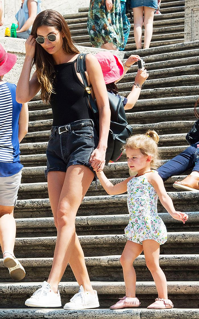 Lily Aldridge wears a black bodysuit with black denim shorts, white sneakers, and sunglasses