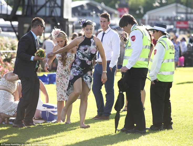 A search party looks for a woman's shoes to complete her otherwise stunning outfit, wearing the signature floral theme for Oaks day