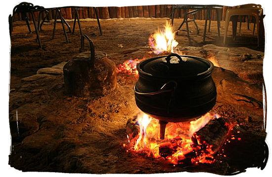 Cooking potjiekos (pot food)over an open fire, highly popular with all South Africa cultures - Delicious Food in South Africa, South African food guide