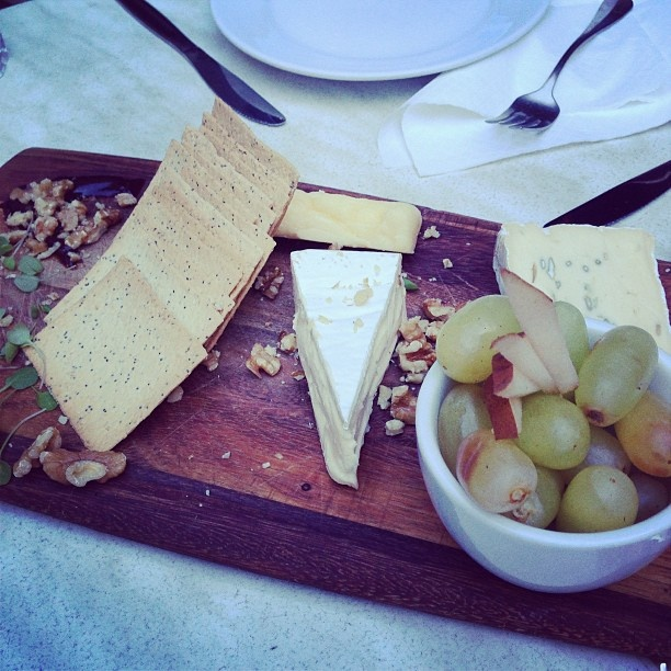 Cheese plate with walnuts, pears, grapes, and quince