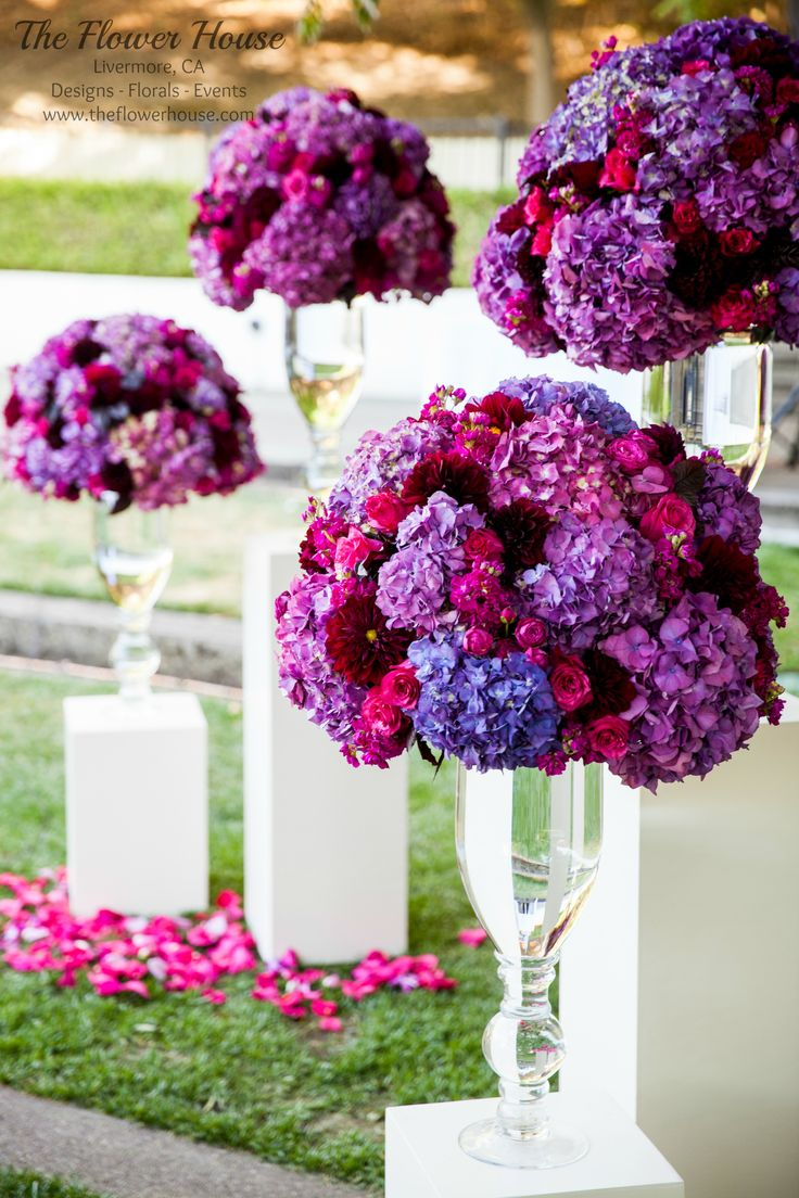 Tall hourglass ceremony arrangements in purples, magentas, and plums. By theflowerhouse.com