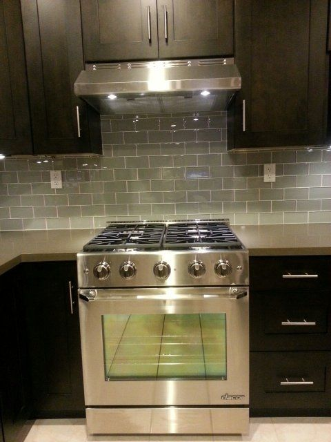 Dark Walnut Pre Fabricated Cabinets Complemented With Color Quartz Stone  And Fog Glass Subway Tile Backsplash