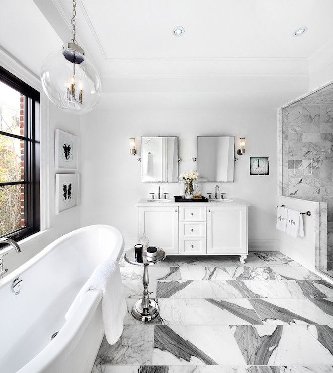Stunning bathroom with freestanding tub below glossy black framed windows illuminated by a Regina Andrew Large Globe Pendant in Nickel Finish hung from tray ceilings. The tub is flanked by a small polished aluminium side table in front of a small white double vanity paired with pivot wall mirrors alongside polished nickel wall sconces. Gray and white square shaped marble tiled floors lead into the walk-in shower with seamless glass surround and marble tiled interior.