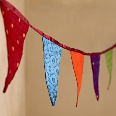 This gorgeous recycled sari bunting will brighten up any room. Our sari bunting is made using the off-cuts from the fabric covers of our sari stationery range.    The recycled sari bunting comes in two lengths – the longer one (280cm) comes with ten large flags, the shorter one (210cm) comes with ten smaller flags.    This is for the Larger version