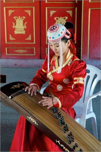 Kraig Lieb - Mongolian woman in traditional clothing playing musical instument Choijin Lama Temple Museum.