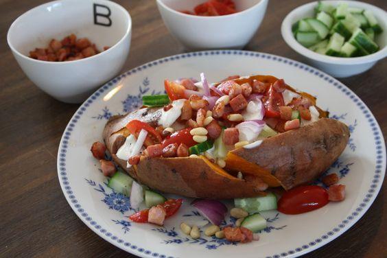 Heerlijk slank recept: Gepofte zoete aardappel met onder andere rode ui, pijnboompitten, komkommer en zelf gemaakte chili saus!