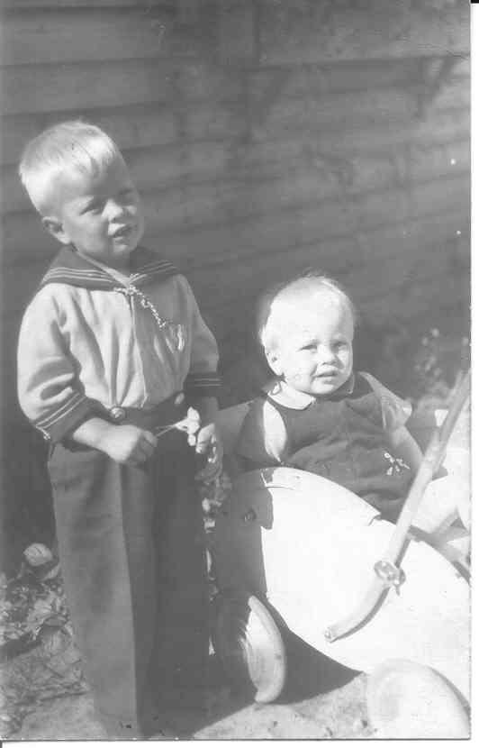 Istun rattaiissa ja isoveljeni Pertti seisoo vierelläni.
