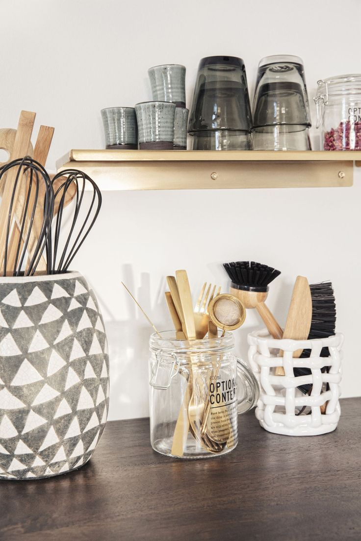 In the tiny kitchen area, open shelves serve double duty as both storage space and decorative statements.