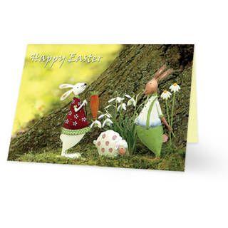 Een paaskaart van twee konijntjes en een schaapje onderaan een boom. Het ene konijntje heeft een wortel in zijn poot, de andere heeft bloemetjes achter zijn rug. Links bovenin staat de tekst ''Happy Easter'' geschreven. Aan de binnenkant van het paaskaartje is de achtergrond een groene waas.