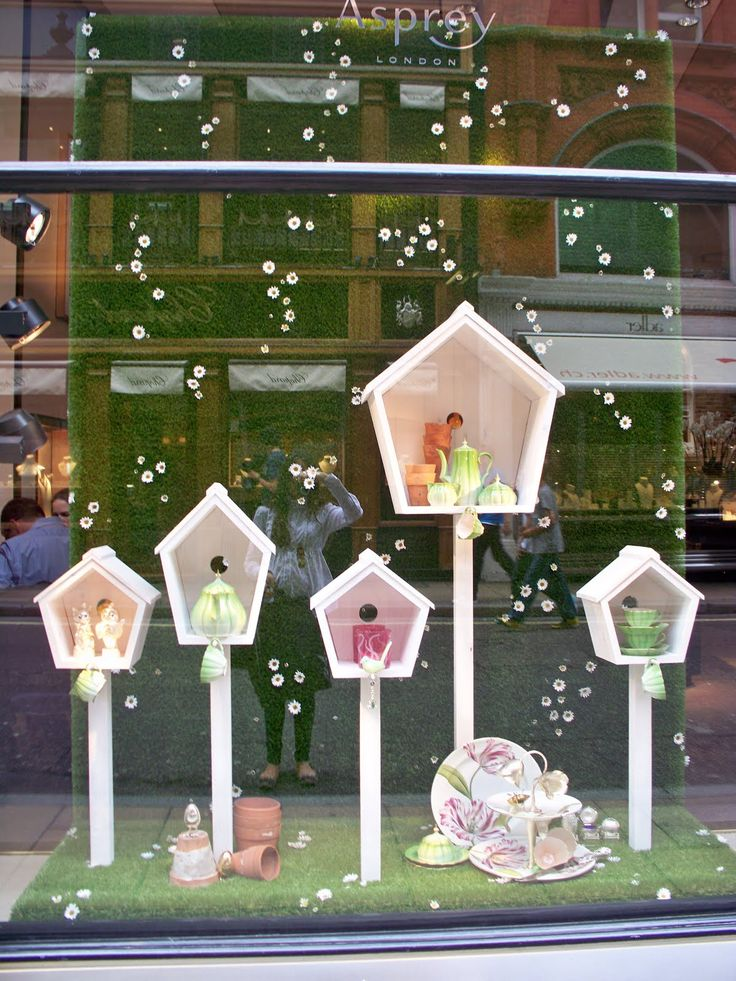 ASPREY | This simple display using white bird houses to display spring product.  I especially like the vertical use of faux grass with daisies as the backdrop. #visualmerchandising #windowdisplays