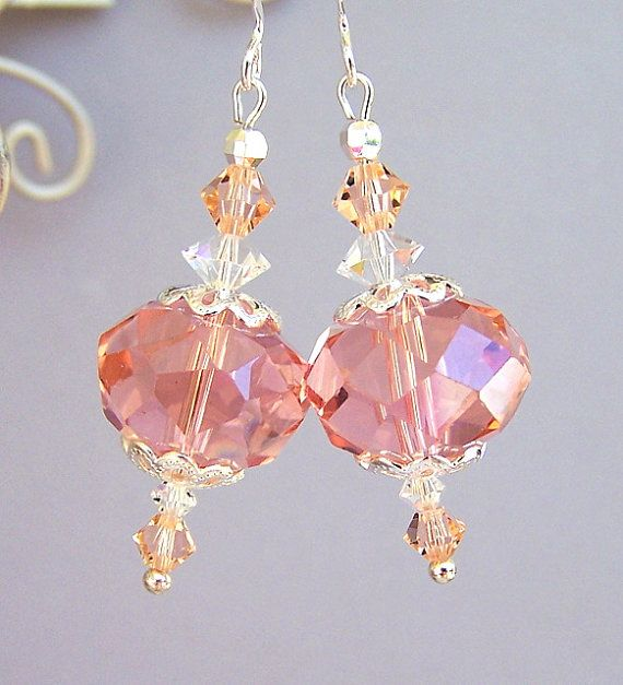 These lovely peachy pink earrings have glass focal beads in a pale peach or pale…