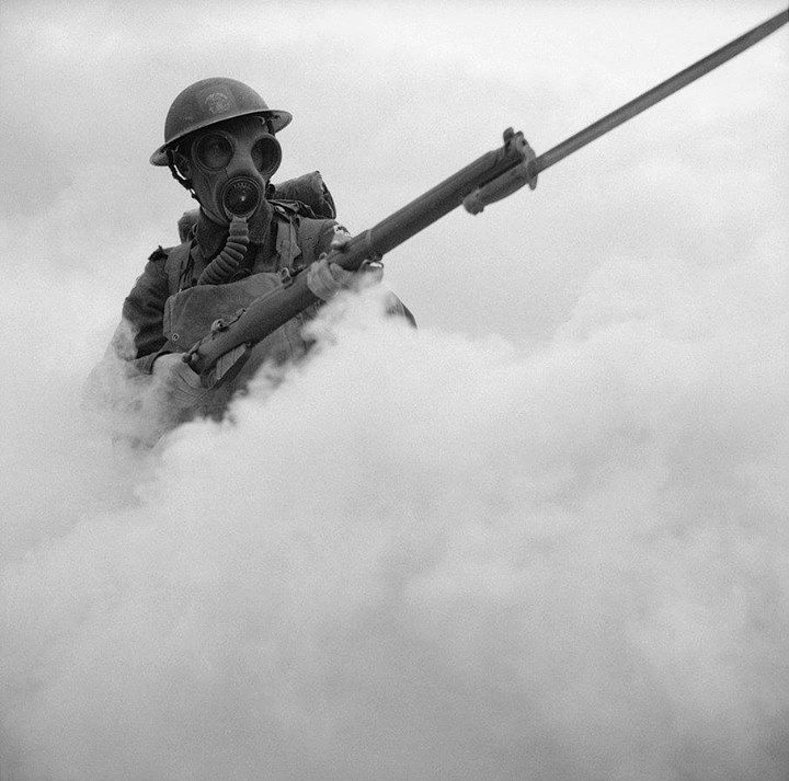 Men of the 12th Battalion Hampshire Regiment in training at Hengistbury Head near Bournemouth Dorset. Wearing his gas mask a soldier advances through a smoke screen.