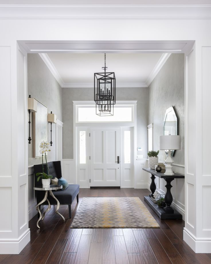 Classic basics: dark stained hardwood, grey walls, white doors/trim, focal pendant fixture. The dark furnishings really pop. But it needs s little color. By Gilmore Design Studio.