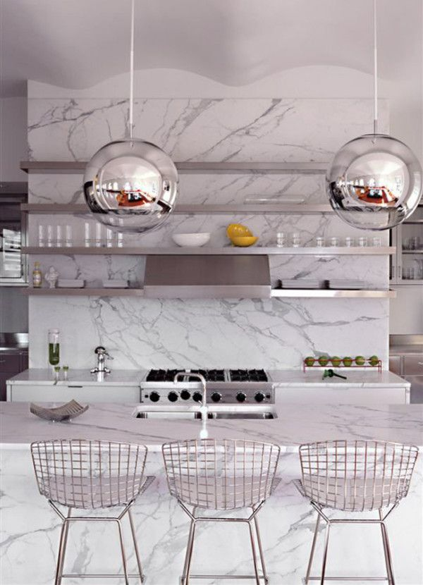12 Kitchen Counters: This Tribeca loft features plenty of Carrara marble—both the island and the back counter is encased. Harry Bertoia's steel rod stools, made by Knoll, is a classic pair up, playing off the stainless appliances, open shelving, and chrome pendants.