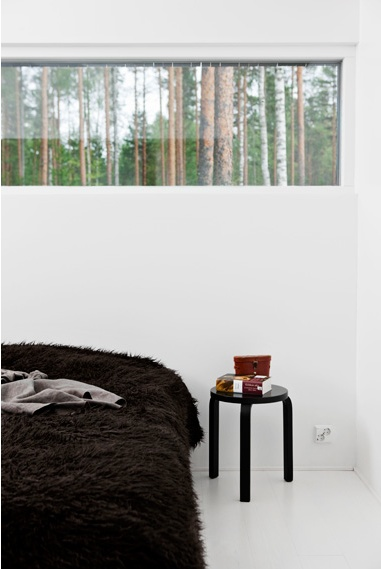 Window above bed with a view to the forest. Cute detail with a black Artek Stool 60 as night table.