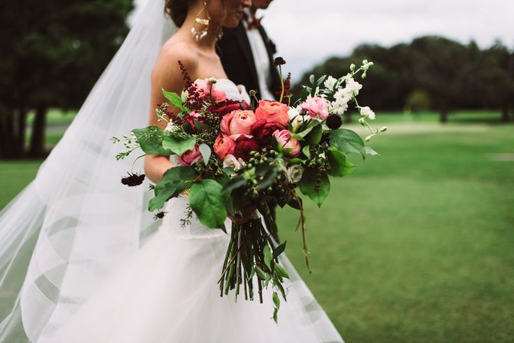 heading to the reception, the bride and groom stroll across the green. her bouquet is a gorgeous loose summer clutch of red charm peony, pink romantic antique garden rose, white majolica spray roses, burgundy scabiosa, burgundy astilbe, pink ranunculus, white larkspur, crepe myrtle, jasmine vine, seeded eucalyptus and lemon leaf.