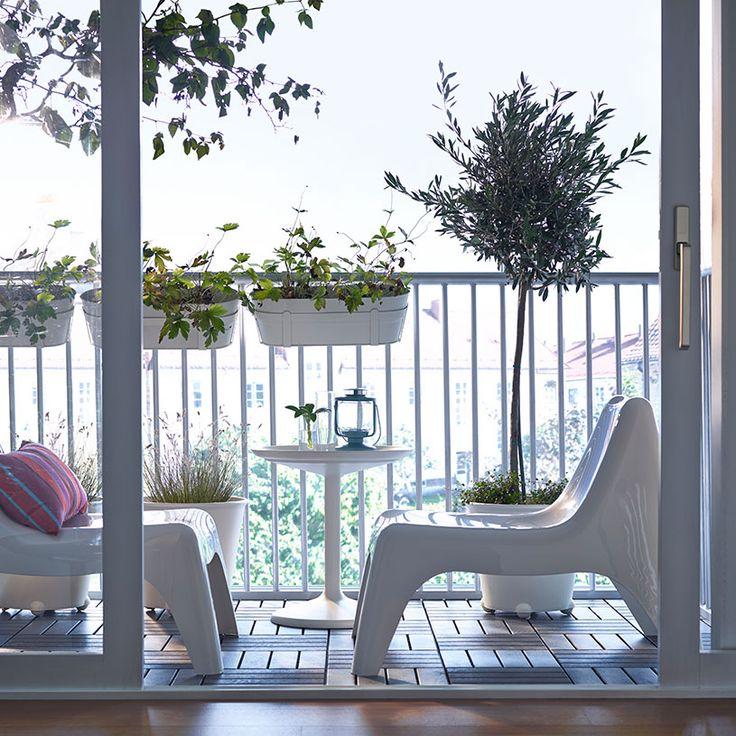Uma varanda com poltronas baixas em plástico, mesa redonda e vasos suspensos, tudo em tons de branco