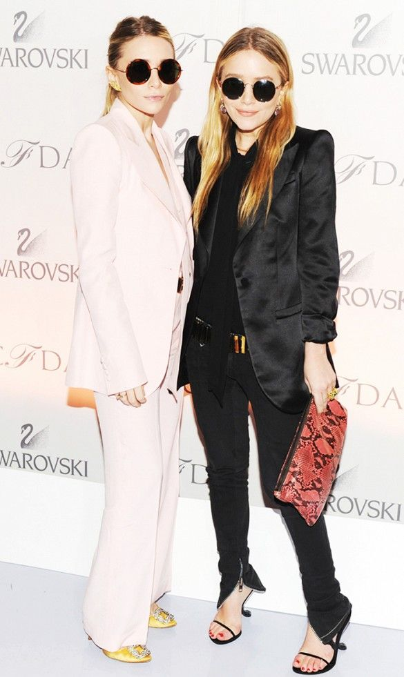 Mary-Kate and Ashley Olsen wear round framed sunglasses with their structured pastel pink and black pantsuits.