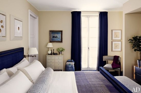 cream walls in guest room with navy comforter, white sheets, navy curtains