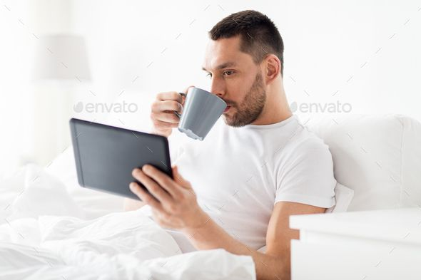 Man With Tablet Pc Drinking Coffee In Bed At Home Coffee In Bed