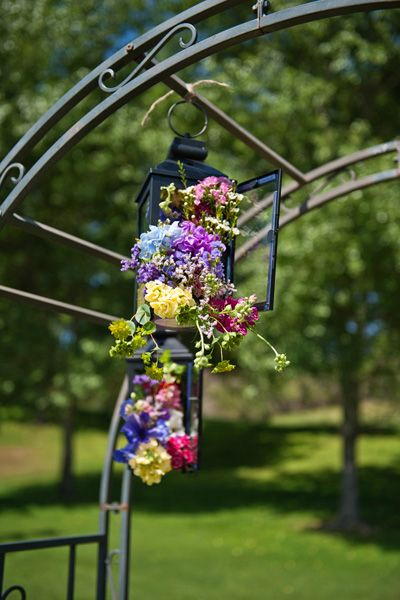 Ceremony Décor - lanterns with wildflowers adorn your ceremony arch. Get your inspiration for a springtime wedding.