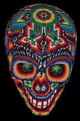 Cráneo con cuentas de colores en el arte huichol mexicano tradicional cordón, símbolo del día de los muertos, aislados en negro Foto de archivo