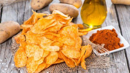 Heap of Paprika Potato Chips on rustic background