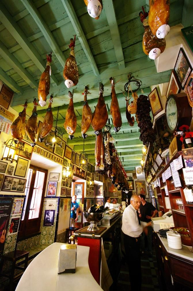 Las Teresas. Sevillian tapas bar. Jamon is hanging from the ceiling. Grease is collected in little umbrellas upside down. Nice idea / so guests don't need to worry about their hair.