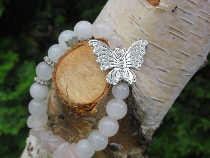 Butterfly   Urocza bransoleta z kul jadeitu białego (1cm) oraz kalcytu o delikatnie bladoróżowej barwie (1cm i 0,8cm), również tego surowego o nieregularnych kształtach. Ozdobą bransolety jest duży (ok. 2cm) motyl w stylu bali. Bransoleta przepięknie wygląda i układa się na nadgarstku.