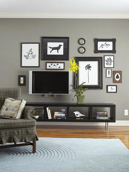 Dramatically display black-and-white art prints on a dark gray wall. A back-to-basics color scheme is a cohesive way to display many different shapes and sizes of images without the arrangement becoming visually overwhelming. Gray walls make the framed and matted prints pop, while additional items -- mirrors and a TV -- in the same color scheme bring dimension to the collage.