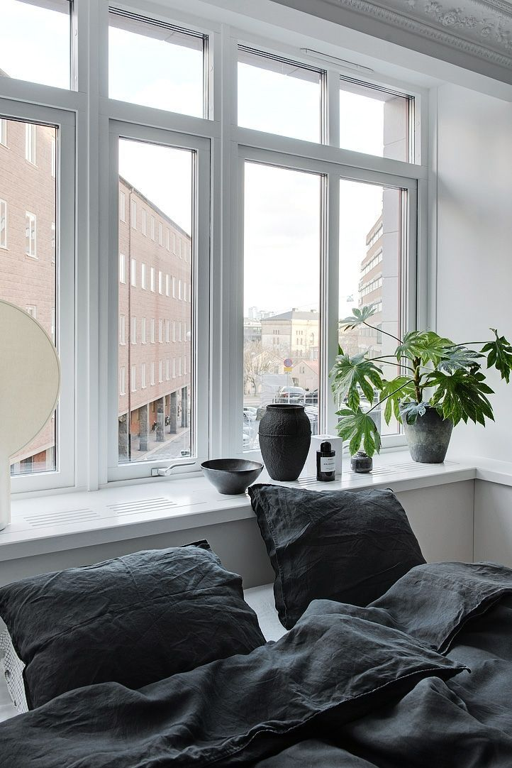 A cosy Scandi style bedroom with trendy blue washed linen sheets, lots of natural light and a green plant by Alvhem