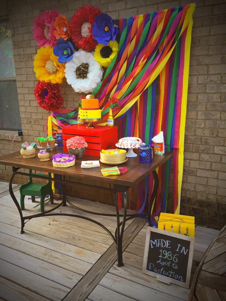 Mexican themed tablescape flower colorful backdrop with two tier fondant cake cactus cupcakes and jello mexican birthday party