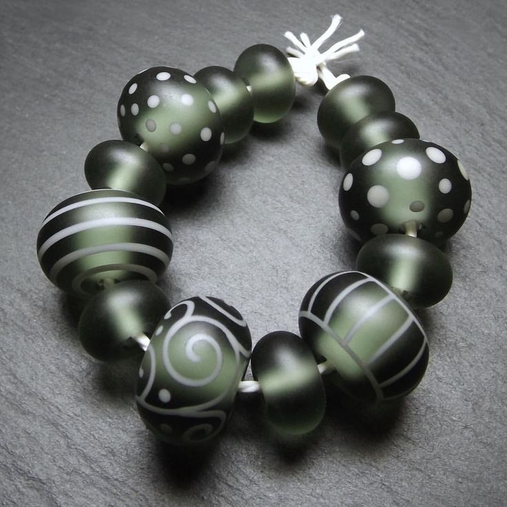Tumble-etched 'Green Smoke' Luminobeads. I really like the subtle greenness of Effetre's Dark Steel Grey. Lovely colour. These beads have been finished with a light application of olive oil and beeswax to really bring out their soft 'glow'. #lampworkglass #lampworkbeads #beadsbylaura #softglass #sodalime #beadsofig #glassbeads #handmade #effetre #greygreen #tumbleetched